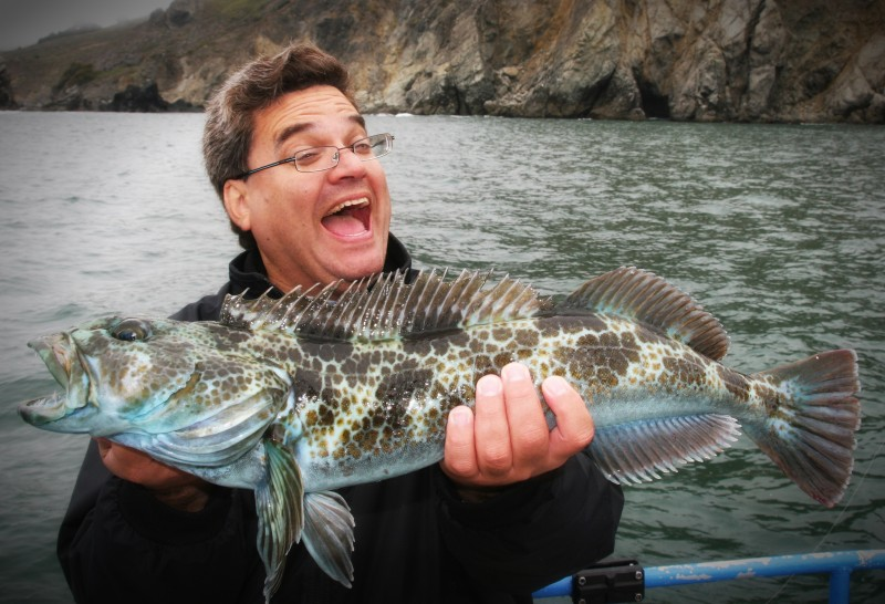 happy fisherman holding his catch on a fishing charter in san francisco